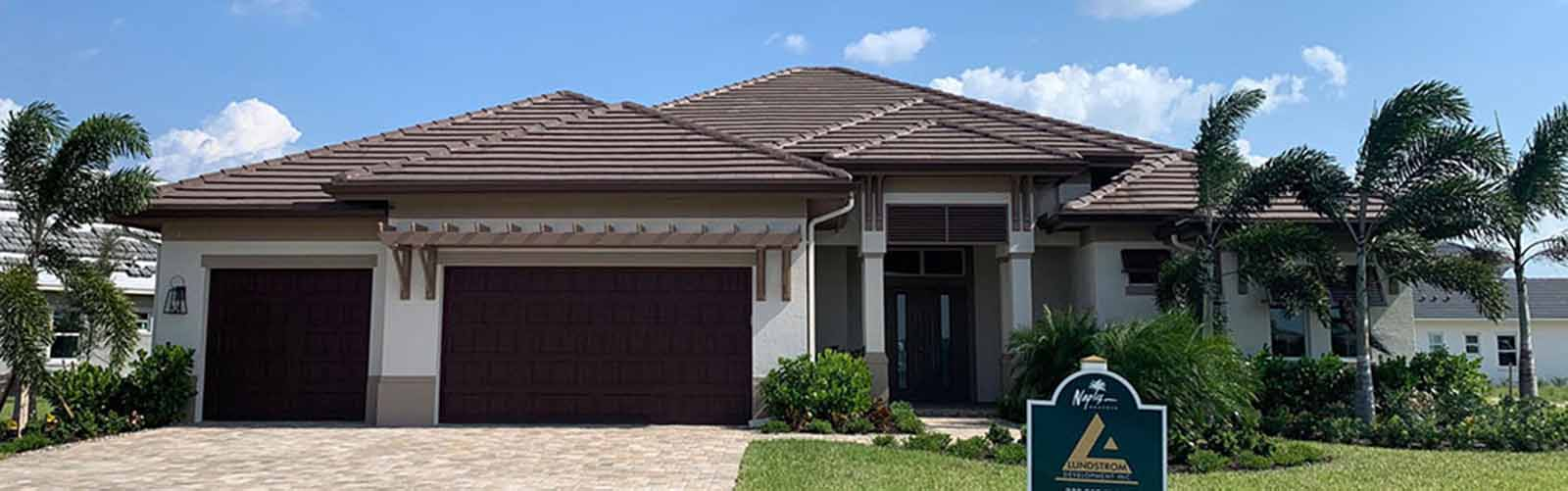 Lundstrom Development New Home at Naples Reserve with brown tile roof and paver driveway